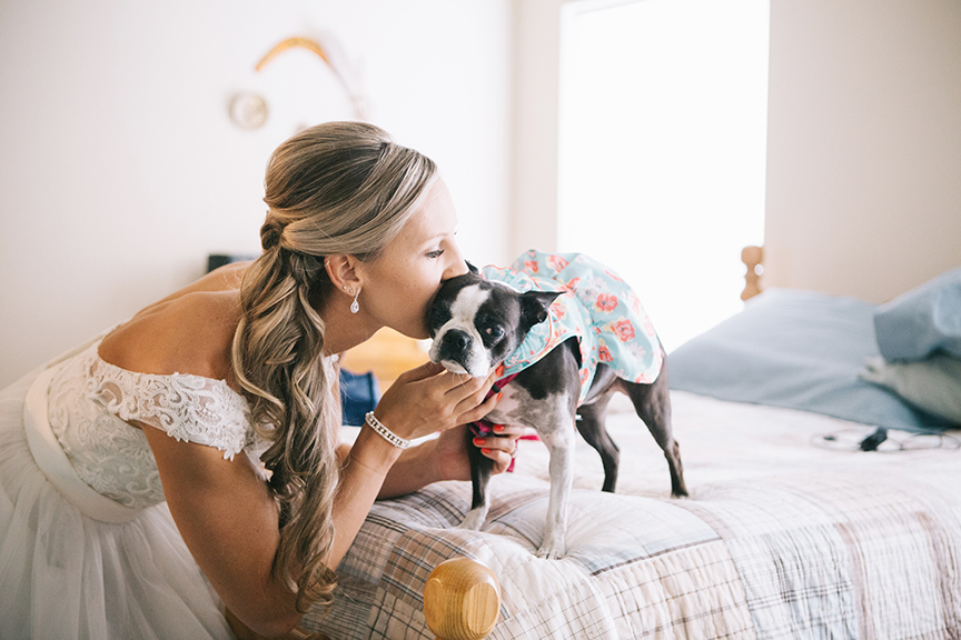 Bride kissing dog backyard wedding