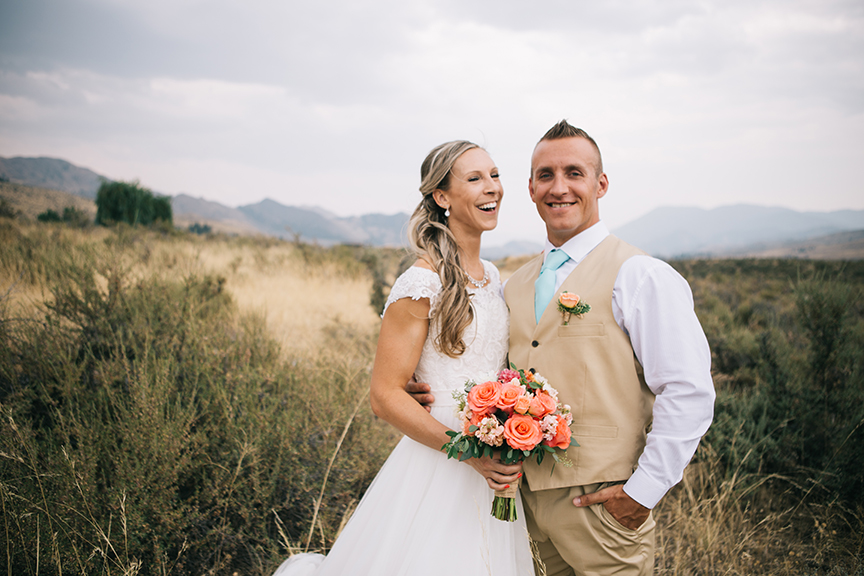 Bride and groom laughing in golden mountain field