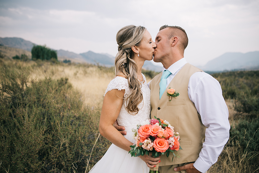 bride and groom kissing in mountain field
