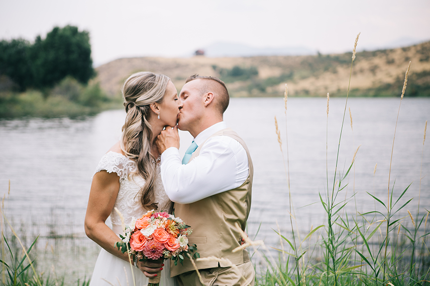 Bride and groom kissing near lake