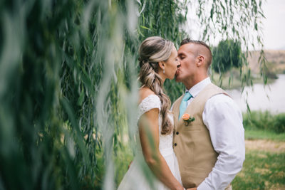 Bride and groom kissing under willow tree
