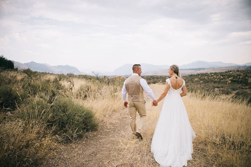 Bride and groom walking through mountain meadow