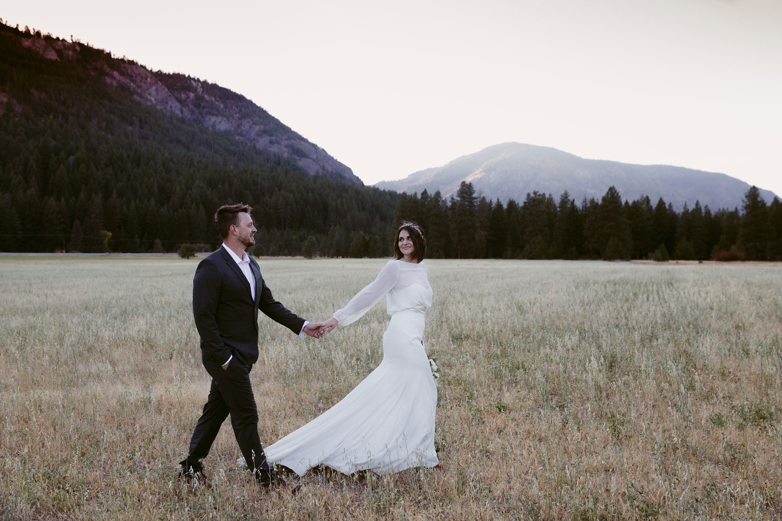 Bride and groom walking through field elopement winthrop wa