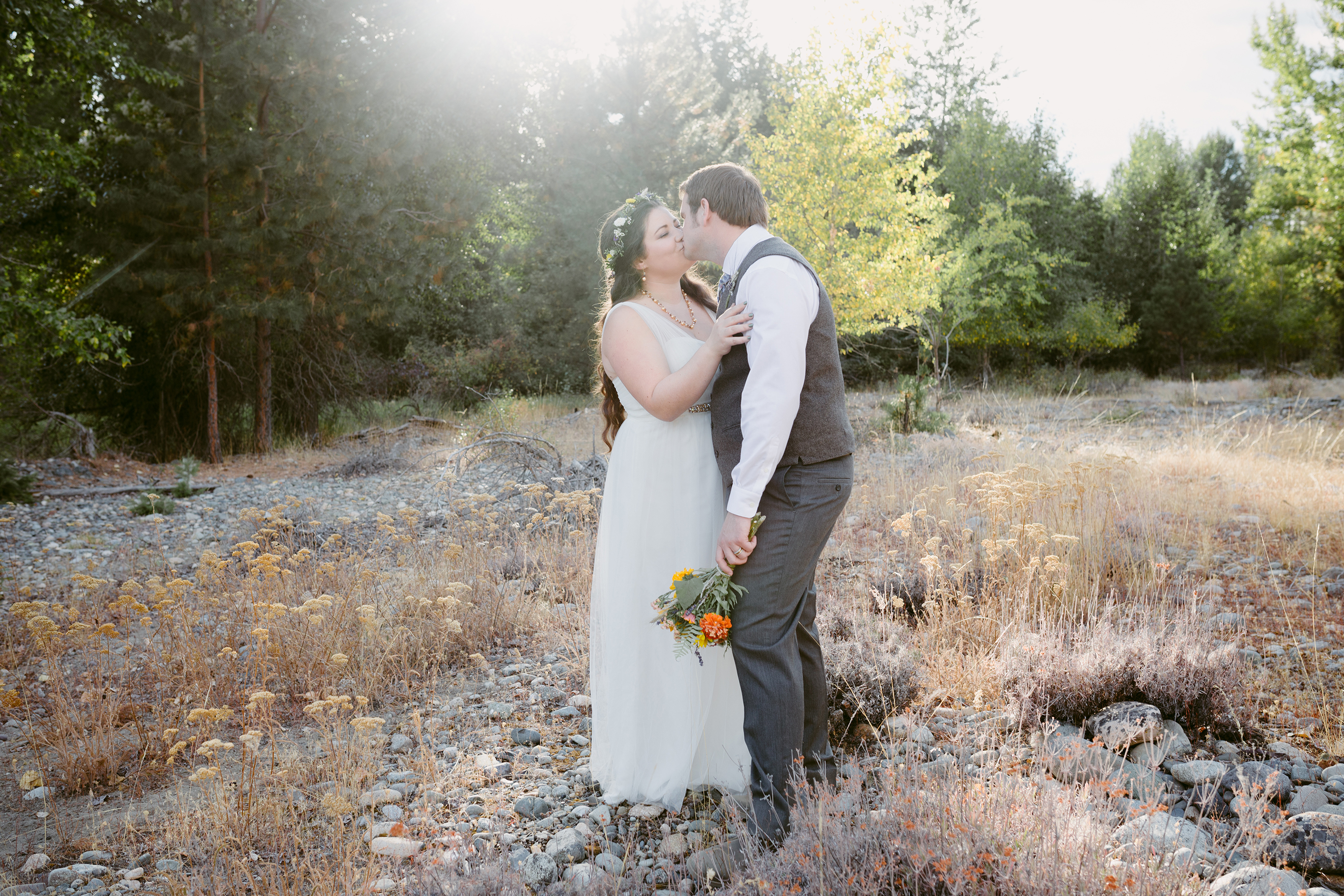 Bride and Groom kiss in forest Spring Creek Ranch Winthrop Wa
