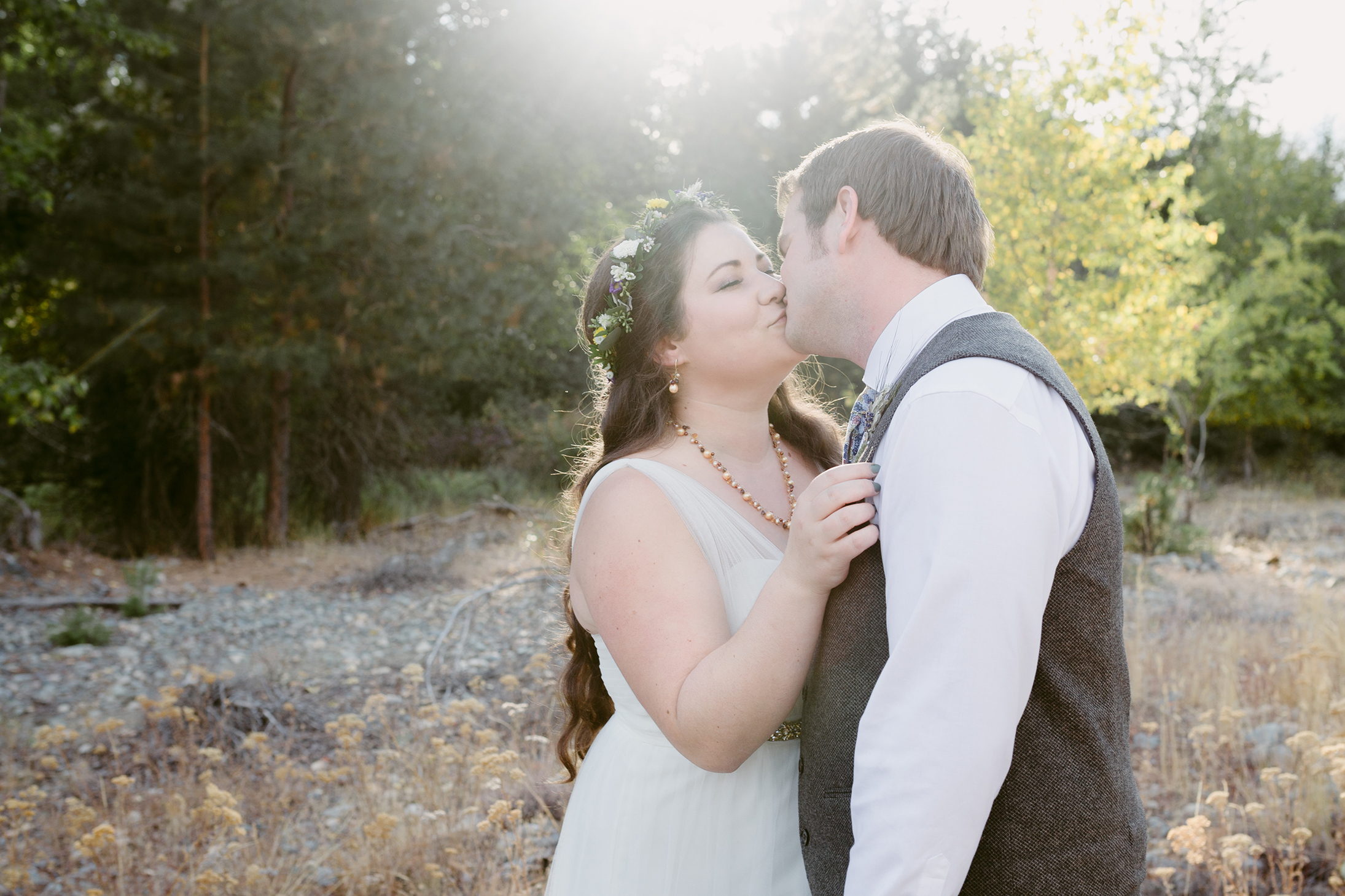 Bride and Groom kiss in forest Spring Creek Ranch Methow Valley
