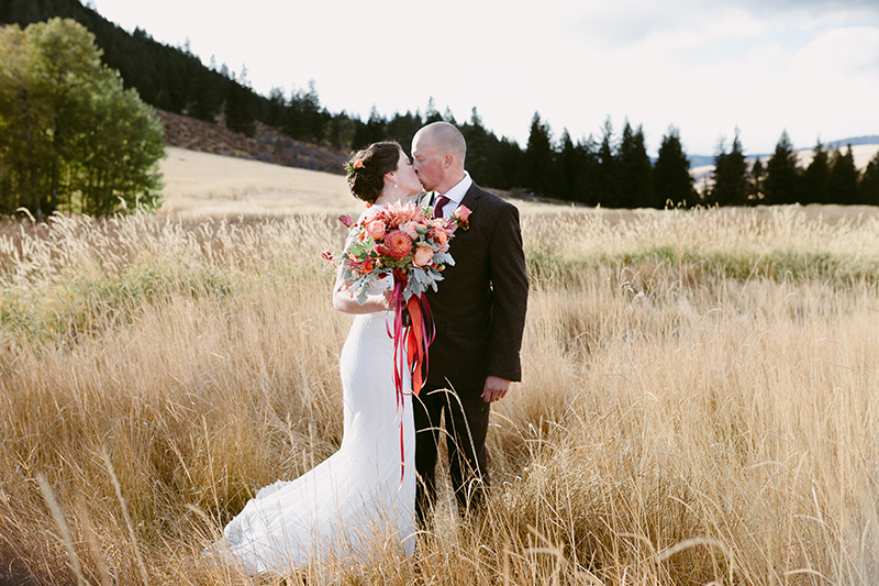 bride and groom kiss in mountain field