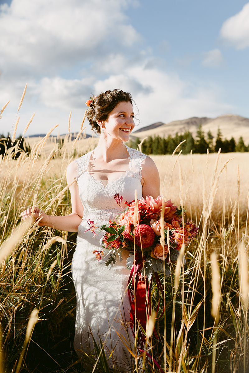 Bride looks at groom in tall grass