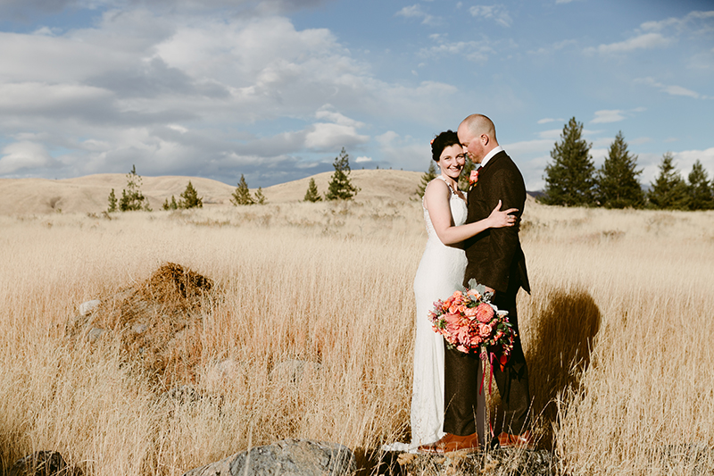 Bride and groom in mountain meadow
