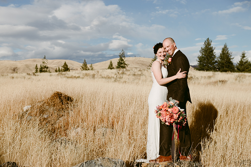 Bride and groom embrace in ranch wedding